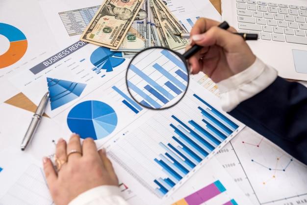 Kobiety ręka trzyma lupę na wykresie biznesowym