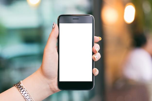 Kobiety ręka trzyma mobilnego smartphones bielu ekran dla mockup projekta i app pokazu backg