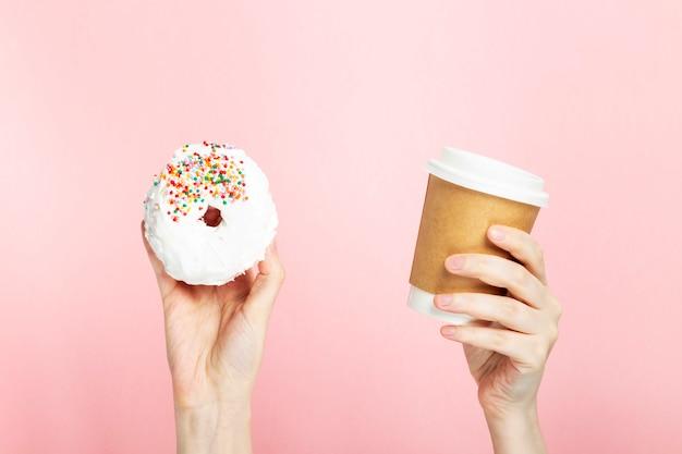 Kobiety ręka trzyma papierową filiżankę z kawą i pączkiem z białym lodowaceniem i stubarwną cukrową ciasta polewą, różowy tło