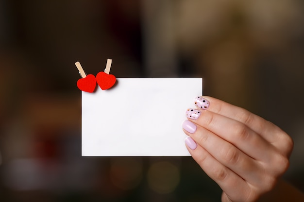 Kobiety ręka trzyma papierową kartę z dwa kierowymi szpilkami. koncepcja walentynki. copyspace dla tekstu.