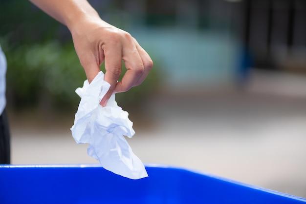 Kobiety ręka trzyma papierowego odpady i wkłada w śmieci kosz.