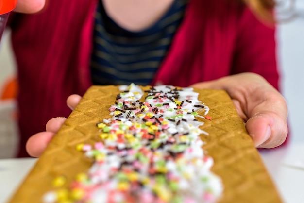 Kobiety ręka trzyma piernikowego ciastko dekorującego z cukierem