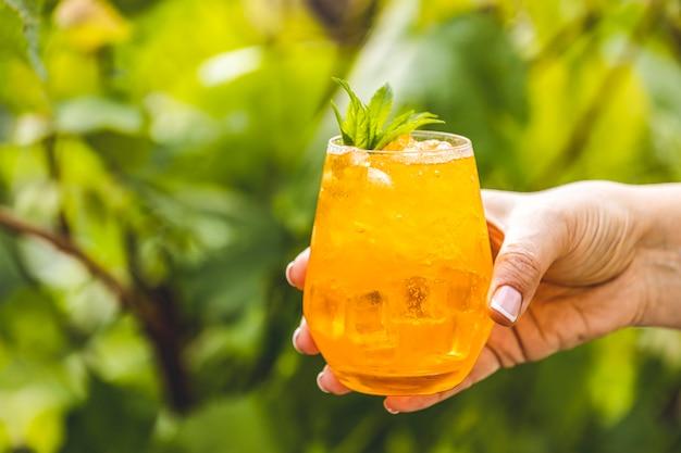 Kobiety ręka trzyma pomarańczowego napój z lodem na lata pogodnym ogrodowym tle