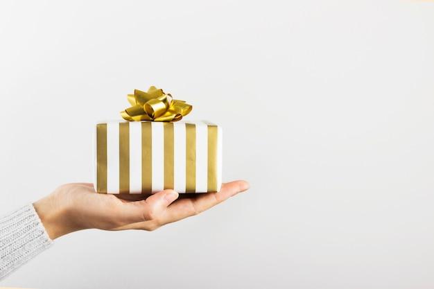 Kobiety ręka trzyma prezent w bielu i złota papierze na popielatym, kopii przestrzeń
