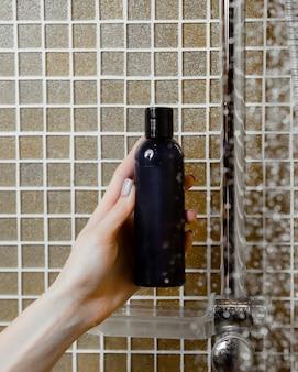 Kobiety ręka trzyma prysznic żel w granatowej butelce w łazience
