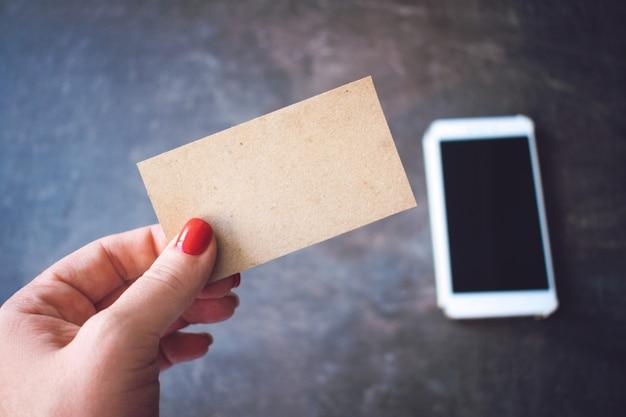 Kobiety ręka trzyma przetwarzającą papierową pustą wizytówkę na defocused smartphone