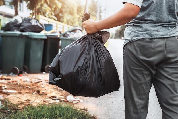 Kobiety ręka trzyma śmieci w czarnej torbie do czyszczenia w śmieci