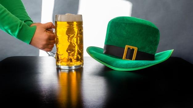 Kobiety ręka trzyma szklankę piwa w pobliżu kapelusza dzień świętego patryka krasnoludek na czarno