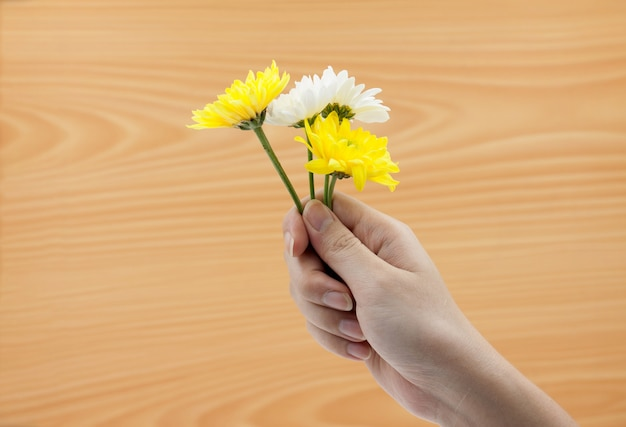Kobiety ręka trzyma wiązkę kwiaty na drewnie