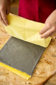 Kobiety ręka usuwa żółtego płótno od papierowej papki