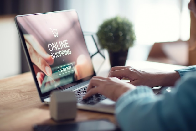Kobiety ręka używać laptop dla robić zakupy zapłatę online w domu.