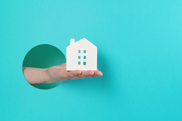 Kobiety ręka w papierowej dziurze trzyma małego zabawka dom