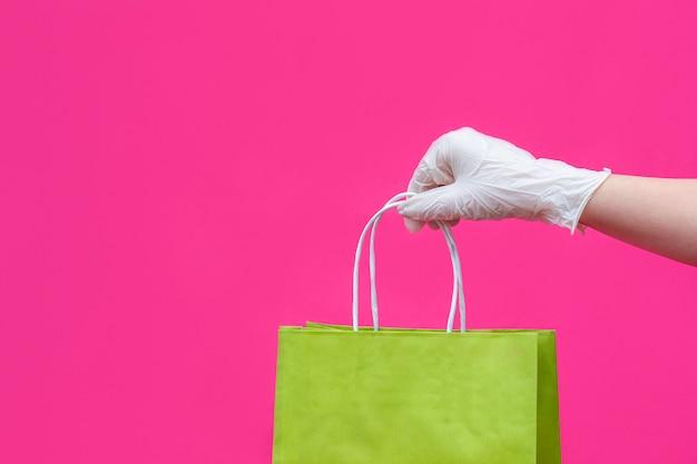 Kobiety ręka w rękawiczce z papierową torbą na menchiach.