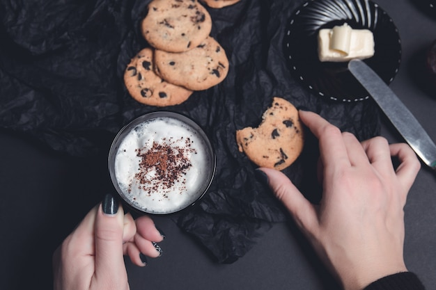 Kobiety ręka z filiżanką kawy lub cappuccino i czekoladowymi ciastkami, ciastka
