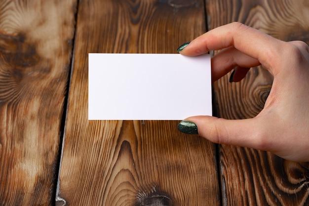 Kobiety ręka z manicure'em trzyma białą wizytówkę nad stół