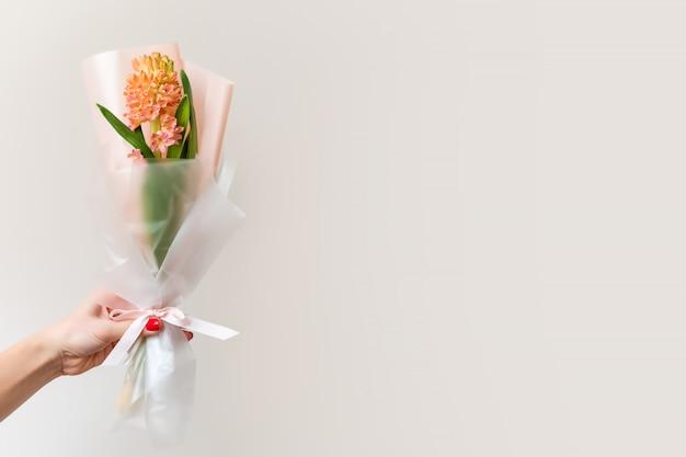 Kobiety ręka z manicure'em trzyma wiosennych kwiaty.