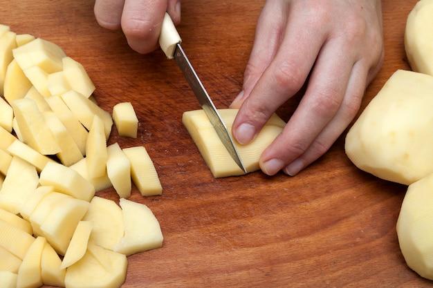 Kobiety ręka z nożem pokrajać grule na drewnianej desce w kuchni.
