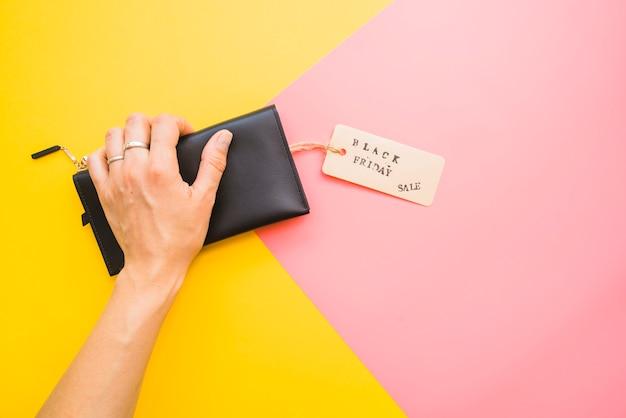 Kobiety ręka z sprzęgłową torbą i etykietką
