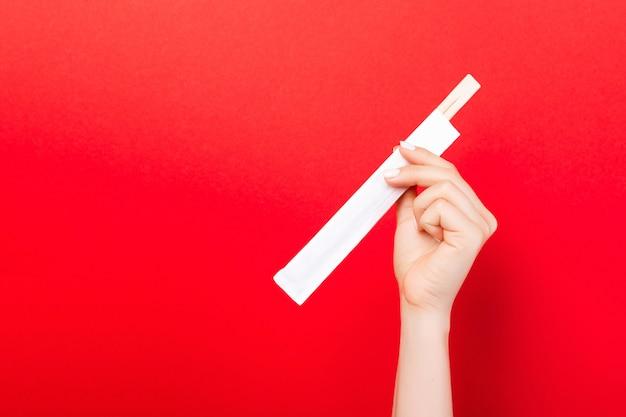 Kobiety ręki mienia chopsticks w paczce na czerwonym tle