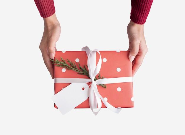 Kobiety ręki mienia czerwony prezenta pudełko i papierowa etykietka odizolowywający na bielu dla bożych narodzeń i.