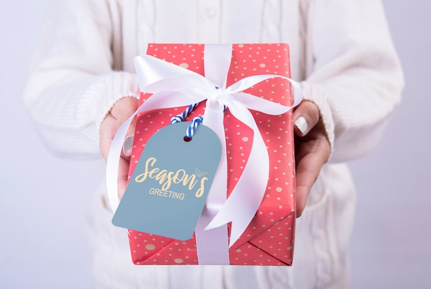 Kobiety ręki mienia prezenta czerwony pudełko i papierowa etykietka odizolowywający na bielu