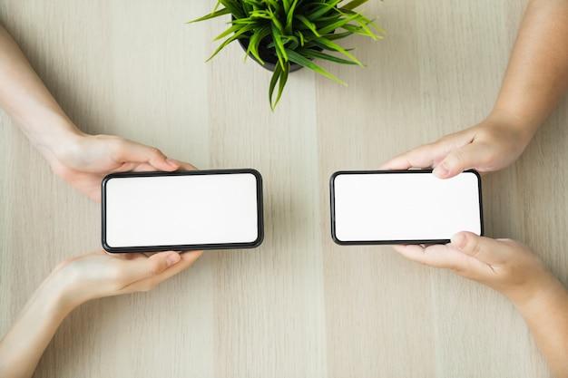 Kobiety ręki mienia smartphone i wzruszający pusty ekran.