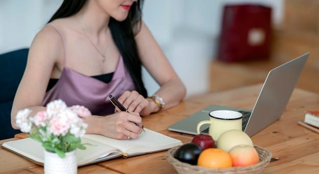 Kobiety ręki writing na notatniku podczas gdy siedzący przy stołem.