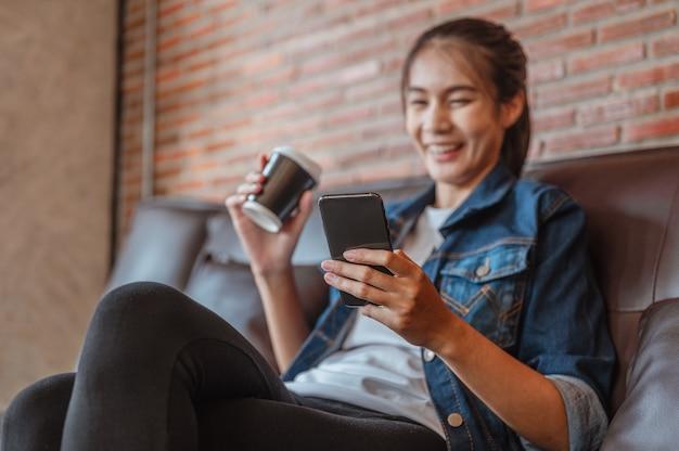 Kobiety relaksują się podczas oglądania lub robienia zakupów na laptopie podczas przerwy na kawę po pracy w kawiarni