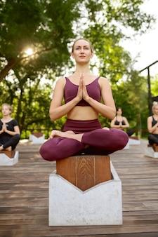 Kobiety relaksują się w pozie jogi, trening grupowy w letnim parku