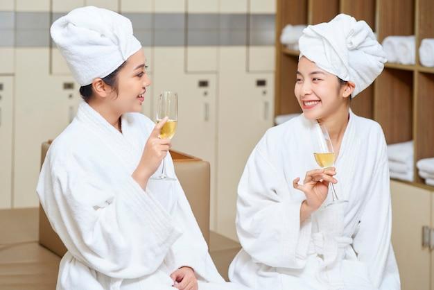 Kobiety relaksujące z szampanem w salonie spa