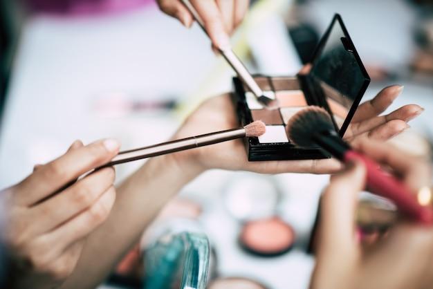 Kobiety robią makijaż z pędzlem i kosmetycznych