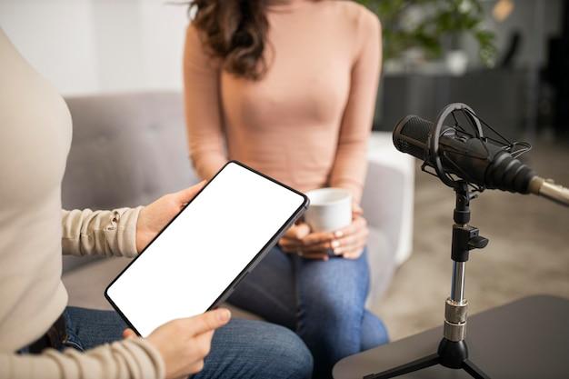 Kobiety robią radio razem z mikrofonem i tabletem