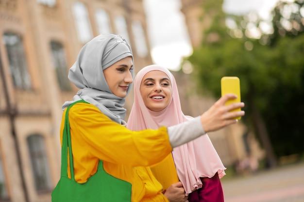 Kobiety robiące selfie. piękne młode muzułmańskie kobiety w hidżabach robiące selfie w pobliżu uniwersytetu