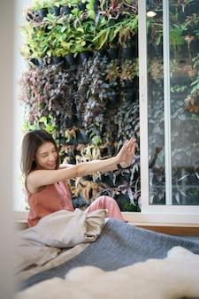 Kobiety rozciąganie w łóżku po budził się ranek, widok z okno na tropikalnym ogródzie.