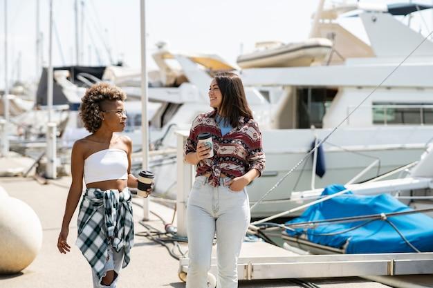 Kobiety rozmawiają o piciu kawy. dwie kobiety pozują w marinie, w tle jachty. dziewczyny wybierają się na morską wycieczkę łodzią