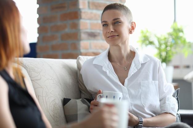 Kobiety rozmawiające siedząc na kanapie w mieszkaniu przerwa na kawę dla pracowników biurowych office