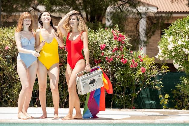 Kobiety różnych narodowości w strojach kąpielowych bawią się w basenie. koncepcja dumy gejowskiej
