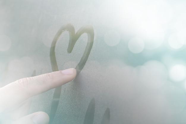 Kobiety rysowane ręcznie kształt serca na szkle okno