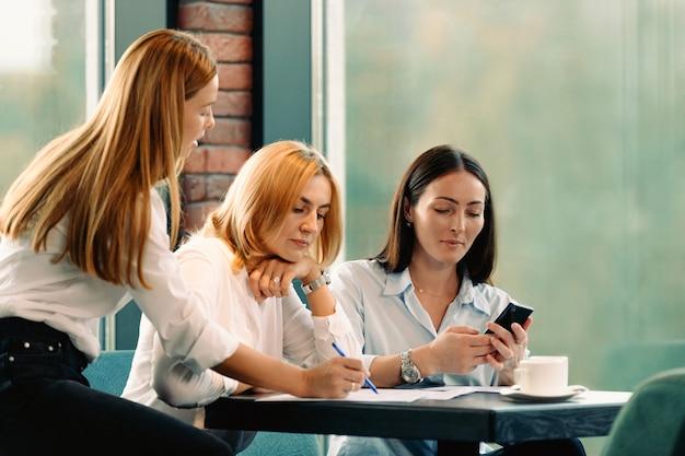 Kobiety siedzą przy stole w biurze, podpisują dokumenty i czytają wiadomości na smartfonie