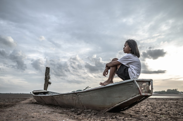 Kobiety siedzą przytulając kolana na łodzi rybackiej i patrzą w niebo na suchym lądzie i globalnym ociepleniu