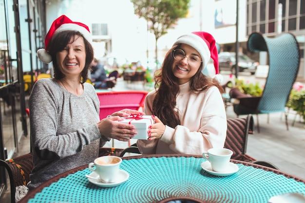 Kobiety siedzą razem w czapkach mikołaja i trzymają razem jeden prezent