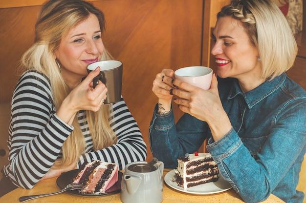Kobiety siedzą w kawiarni i piją gorącą herbatę