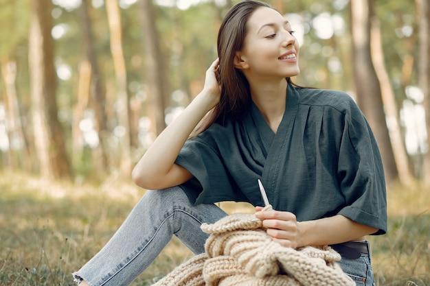 Kobiety siedzą w letnim parku i robią na drutach