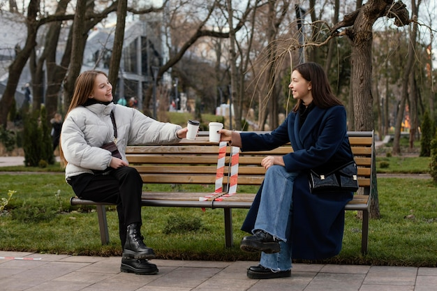 Kobiety siedzące na odległość i noszące maskę
