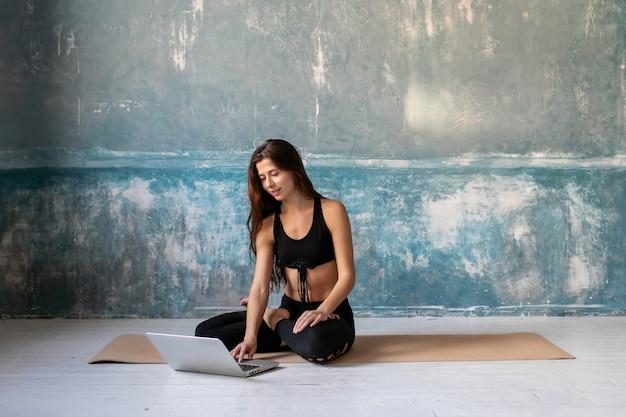 Kobiety siedzące na zajęciach jogi na macie fitness, oglądając filmy fitness za pomocą laptopa.