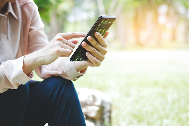 Kobiety siedzące, naciskając czarne telefony komórkowe, by skontaktować się z klientem.