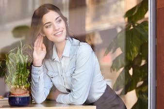 Kobiety siedzieć salowy w miastowej kawiarni patrzeje przez okno