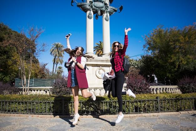 Kobiety skaczące w pobliżu pomnika