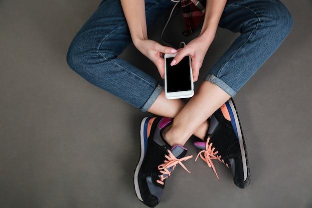 Kobiety skrzyżowane nogi i ręce trzymając pusty ekran telefonu komórkowego