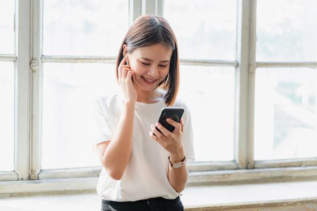 Kobiety słuchają muzyki z białych słuchawek. za pomocą dotyku rąk korzystasz z różnych funkcji, radosnego nastroju.